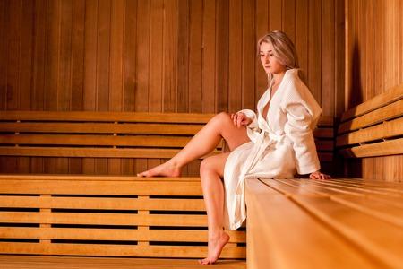 sauna nackt: Sch�ne Frau sitzt in einer h�lzernen Sauna wei�en Mantel entspannt.