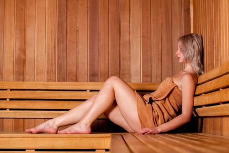 Beautiful woman sitting relaxed in a wooden sauna in a brown towel. Stock Photo