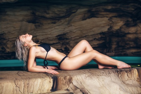 women body: Happy young woman in swimsuit enjoying sitting in cave near the lake. Stock Photo