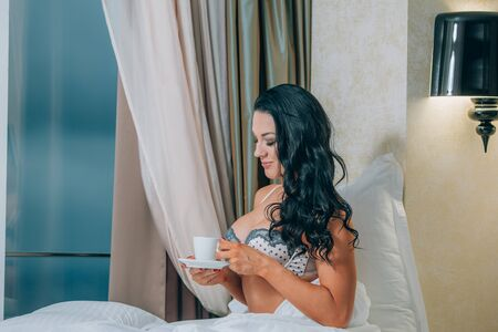 nightwear: Portrait of beautiful young woman in nightwear holding coffee cup on bed Stock Photo