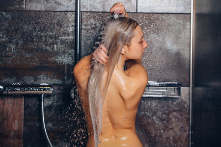 Beautiful woman standing at the shower. Woman is washing her hair.