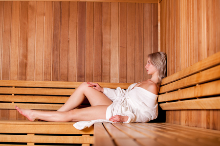 sauna: Beautiful woman sitting relaxed in a wooden sauna white coat.