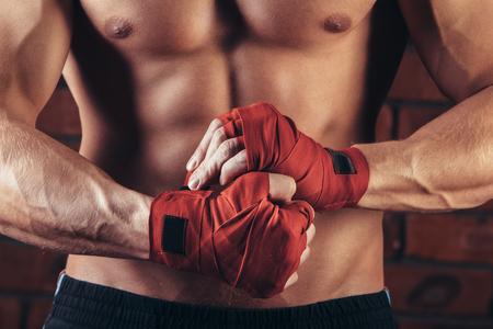 Combatiente muscular con vendas rojas contra el fondo de una pared de ladrillo.