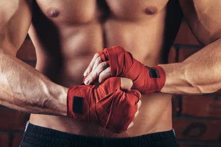arts: Muscular Fighter With Red Bandages against the background of a brick wall.