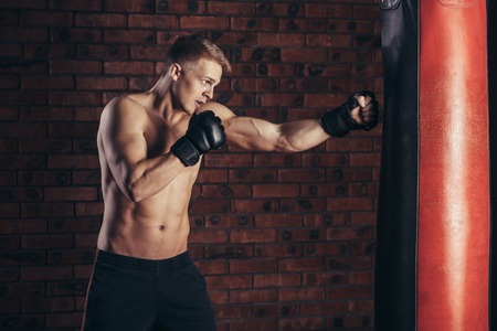 man gym: Boxer training on a punching bag in the gym