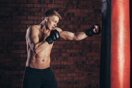 hombre fuerte: la formaci�n del boxeador en un saco de boxeo en el gimnasio
