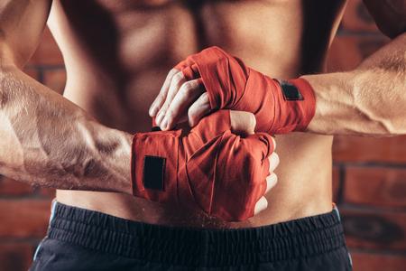 musculoso: Combatiente muscular con vendas rojas contra el fondo de una pared de ladrillo.