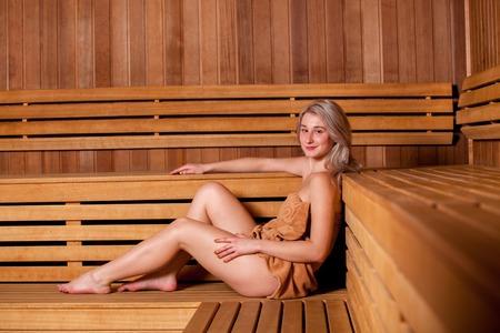 Schöne Frau in einer hölzernen Sauna in einem braunen Tuch sitzt entspannt.
