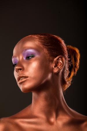 gilt: Gilt. Golden Womans Face Closeup. Futuristic Gilded Make-up. Painted Skin bronze Stock Photo