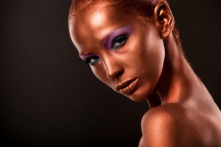 Gilt. Golden Womans Face Closeup. Futuristic Gilded Make-up. Painted Skin bronze Stock Photo