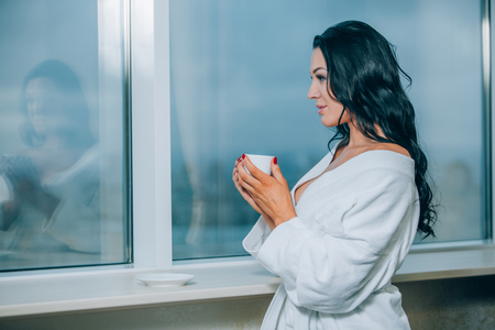 attractive girl: Getting warm with fresh coffee. Beautiful young woman in white bathrobe drinking coffee and looking through a window.