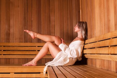 Beautiful woman sitting relaxed in a wooden sauna white coat.