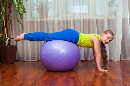 Kid doing fitness exercises. Child  with  on the ball for fittnesa at home. Фото со стока