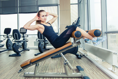 sit ups: Beautiful woman doing press fitness exercise at sport gym. doing sit ups in gym
