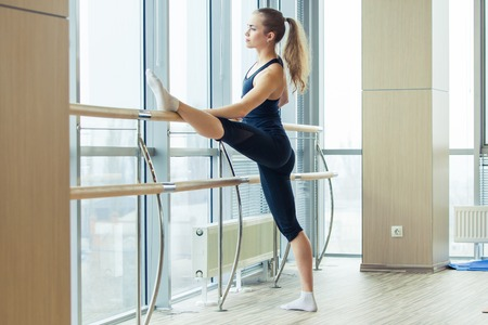 Woman standing near barre in fitness center. in the hall girl doing stretching near Barre.