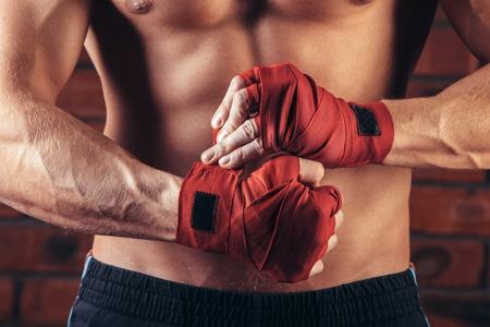 ?  ?      ?  ?     ?  ?    ?  ? gloves: Combatiente muscular con vendas rojas contra el fondo de una pared de ladrillo.