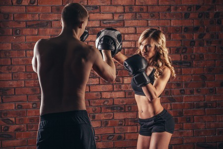 strong women: Cute brunette woman training with boxing gloves at the gym against brick wall. Stock Photo