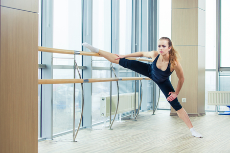 barre: Woman standing near barre in fitness center. in the hall girl doing stretching near Barre.
