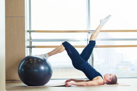 muskeltraining: Fitness, Sport, Training und Lifestyle-Konzept - Frau auf einem Fitness-Ball in einem Fitness-Studio