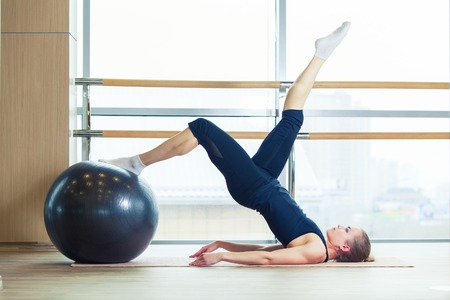 fitness ball: fitness, sport, training and lifestyle concept - Woman on a fitness ball in a gym