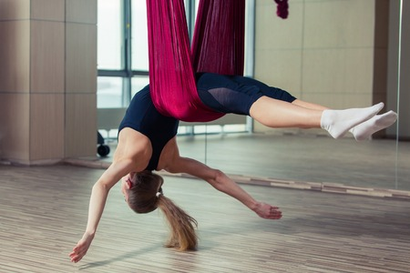 Aerial yoga practicing - anti gravity yoga with scarves.