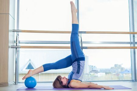 young girl nude: Pilates woman stability ball exercise workout at gym indoor.