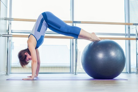 beautiful woman body: Young and athletic girl using fitness ball in a gym. Fitness ball at gym workout fitness and pilates exercise.Young woman doing some pilates exercises with a ball. Stock Photo