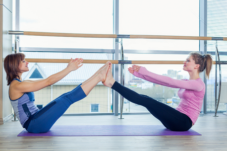 Aerobics Pilates personal trainer helping women group in a gym class.