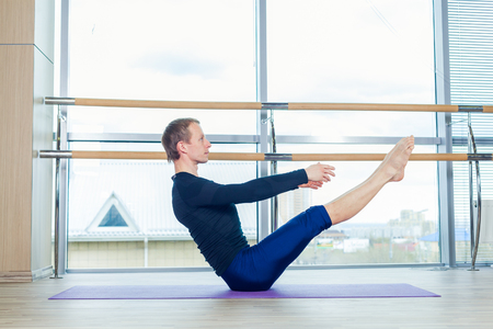 background people: Sporty young man working out, yoga, pilates, fitness training, standing in asana eka pada adho mukha svanasana, one legged downward facing dog pose