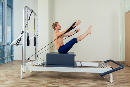 sexy girl: Pilates reformer workout exercises man at gym indoor Stock Photo