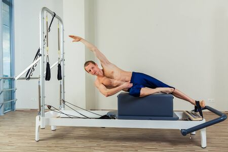 reformer: Pilates reformer workout exercises man at gym indoor Stock Photo
