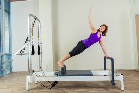 slim body: Pilates reformer workout exercises woman brunette at gym indoor. Stock Photo