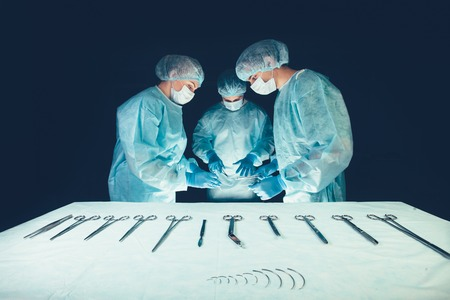scrub cap: Medical team in hospital performing operation. Group of surgeon at work in operating theatre room. healthcare Surgical tools lying on table.Steel medical instruments ready to be used. Surgery and emergency concept
