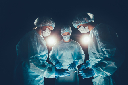 resuscitate: Medical team in hospital performing operation. Group of surgeon at work in operating theatre room. healthcare