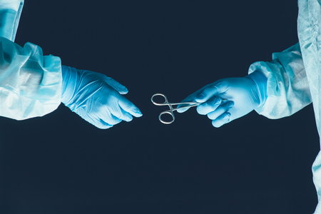 surgical equipment: Two surgeons working and passing surgical equipment in the operating room hospital healthcare Stock Photo