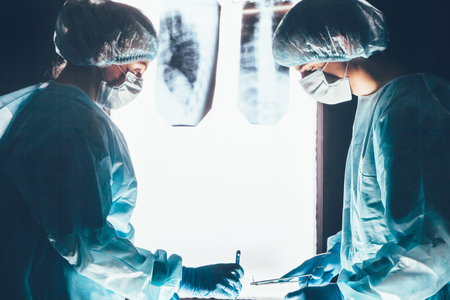 bioclean: Two surgeons working and concentrating at operating table. Medical team in hospital performing operation. Group of surgeon at work in operating theatre room. healthcar. against the background of the spine X-rays Stock Photo