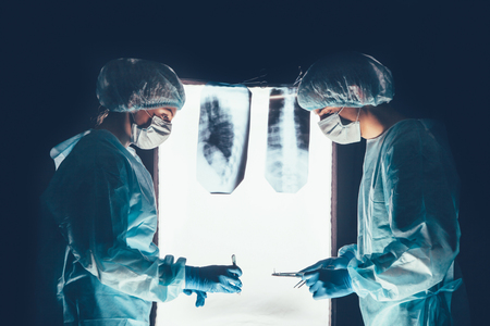 operation theatre: Two surgeons working and concentrating at operating table. Medical team in hospital performing operation. Group of surgeon at work in operating theatre room. healthcar. against the background of the spine X-rays Stock Photo