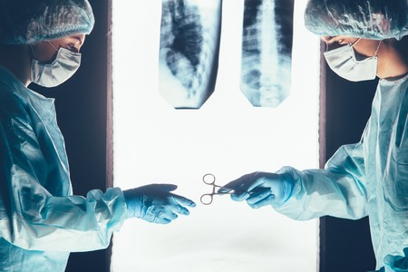 surgical equipment: Two surgeons working and passing surgical equipment in the operating room hospital healthcare  against the background of the spine X-rays Stock Photo