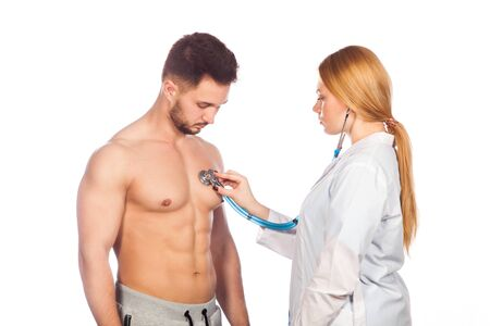 office visit: Doctor listening to young patient chest with stethoscope in his office at the hospital