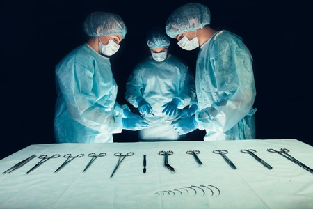 operation theatre: Medical team in hospital performing operation. Group of surgeon at work in operating theatre room. healthcare Surgical tools lying on table.Steel medical instruments ready to be used. Surgery and emergency concept