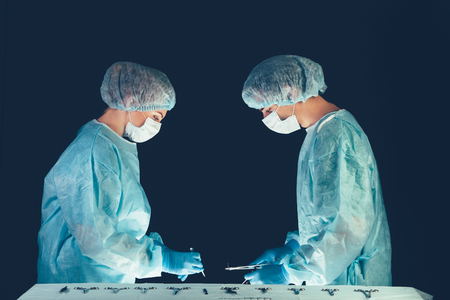 resuscitate: Medical team in hospital performing operation. Group of surgeon at work in operating theatre room. healthcare  Surgical tools lying on table.Steel medical instruments ready to be used. Surgery and emergency concept