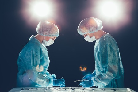 resuscitate: Medical team in hospital performing operation. Group of surgeon at work in operating theatre room. healthcare  Bright light in the frame artistic effect