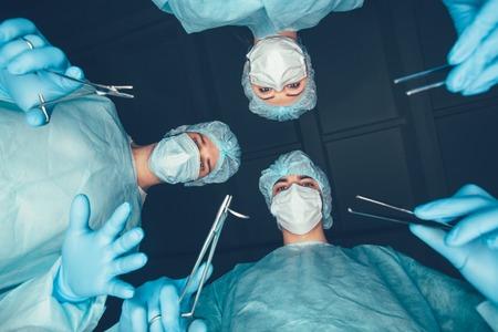 cirujano: Equipo médico en el hospital de realizar la operación. Grupo de cirujano en el trabajo en la sala de quirófano. cuidado de la salud