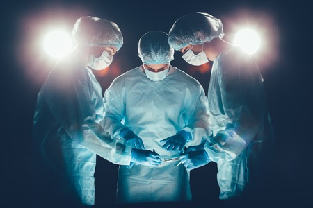 operation theatre: Medical team in hospital performing operation. Group of surgeon at work in operating theatre room. healthcare  Bright light in the frame artistic effect