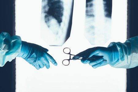 resuscitate: Two surgeons working and passing surgical equipment in the operating room hospital healthcare  against the background of the spine X-rays Stock Photo