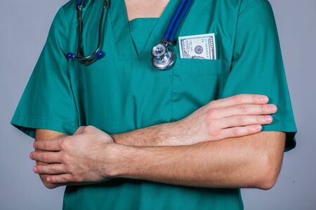 one hundred dollar bill: Doctors scrub top with stethoscope and one hundred dollar bill Stock Photo