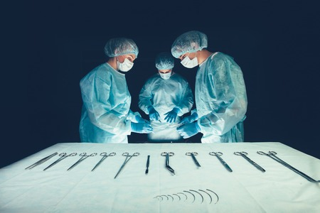 bioclean: Medical team in hospital performing operation. Group of surgeon at work in operating theatre room. healthcare Surgical tools lying on table.Steel medical instruments ready to be used. Surgery and emergency concept