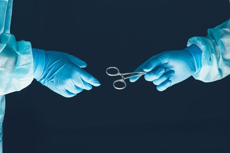by pass surgery: Two surgeons working and passing surgical equipment in the operating room hospital healthcare Stock Photo