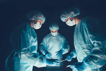 bioclean: Medical team in hospital performing operation. Group of surgeon at work in operating theatre room. healthcare