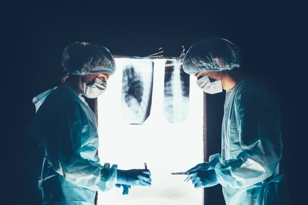 operating table: Two surgeons working and concentrating at operating table. Medical team in hospital performing operation. Group of surgeon at work in operating theatre room. healthcar. against the background of the spine X-rays Stock Photo
